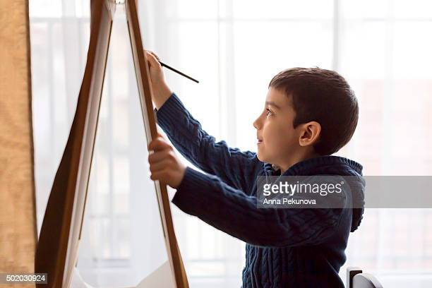 Waist-up portrait of young boy drawing at home