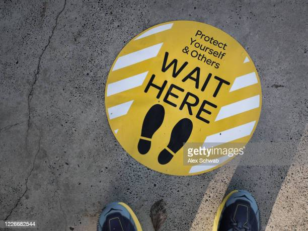 wait here - covid-19 signage - new zealand stock pictures, royalty-free photos & images