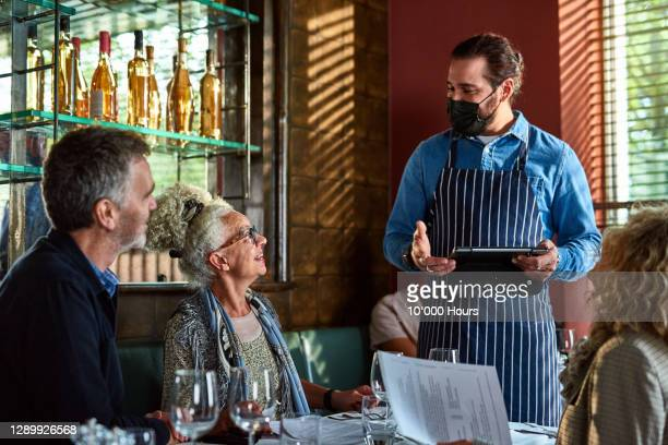 waiter advising senior woman in restaurant - social gathering stock pictures, royalty-free photos & images