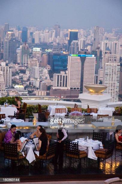 Waiter and diners at Sirocco, with city skyline beyond.