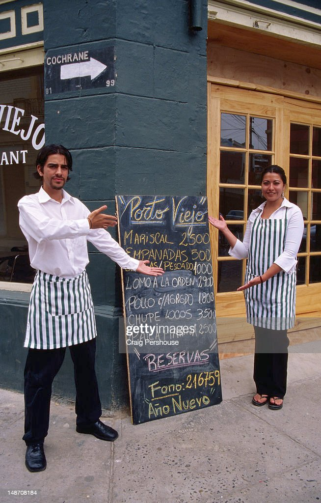 Waiter And Waitress Displaying Menu Del Dia Outside Porto Viejo
