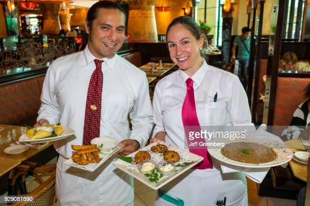 A waiter and waitress serving food from the Cheesecake Factory at The Mall at Millenia