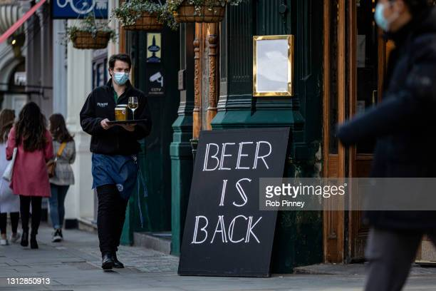 Waiter at a pub carries a tray of drinks to a table on April 16, 2021 in London, England. Pubs and Restaurants are expecting good business tonight...