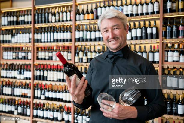Waiter at a restaurant holding a wine bottle and wine glasses looking at camera smiling