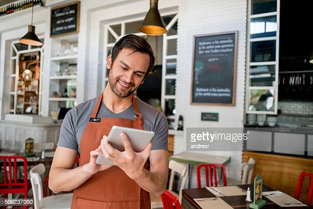 waiter at a restaurant using a tablet computer - wait staff stock pictures, royalty-free photos & images
