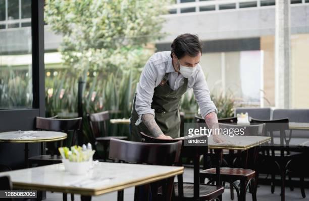 kelner bij een restaurant dat een gezichtsmasker draagt en de lijsten schoonmaakt - voedingsindustrie stockfoto's en -beelden