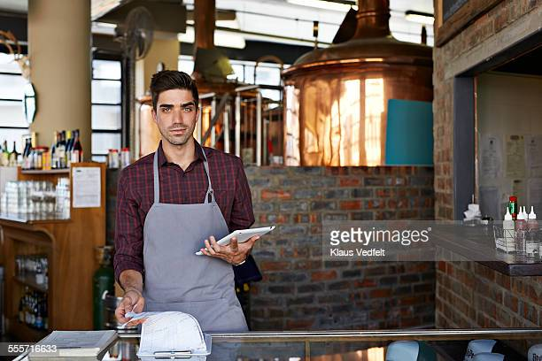 Waiter at microbrewery holding digital tablet