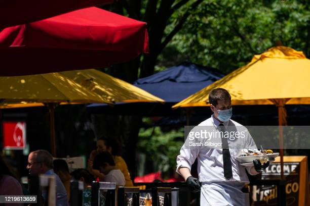 Waiter at Mon Ami Gabi, a French restaurant in Maryland, wears a protective face mask as they serve customers outdoors amid the coronavirus pandemic...