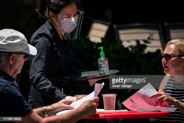 Waiter at Raku, an Asian restaurant in Bethesda, provides hand sanitizer and wears a protective face mask as they work amid the coronavirus pandemic...