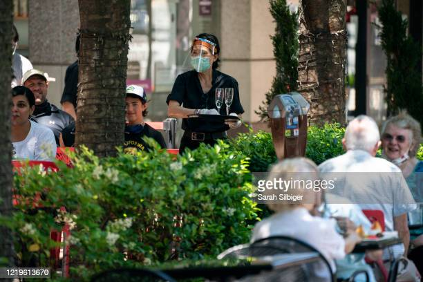 Waiter at Raku, an Asian restaurant in Bethesda, wears a protective face mask as serve customers outdoors amid the coronavirus pandemic on June 12,...