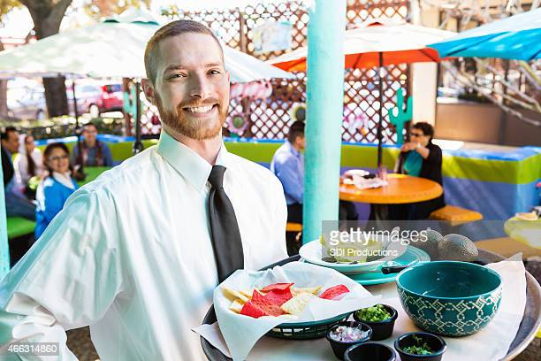 Waiter at Tex-Mex restaurant serving chips to customers on patio
