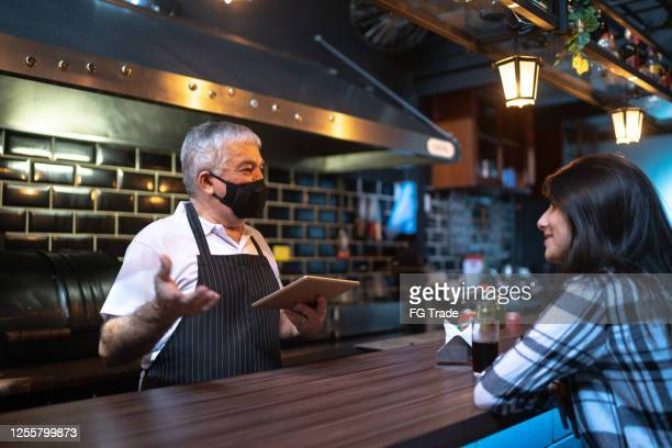 een kelner achter de balie die de bestelling van de klant in een restaurant neemt - beschermend masker werkkleding stockfoto's en -beelden
