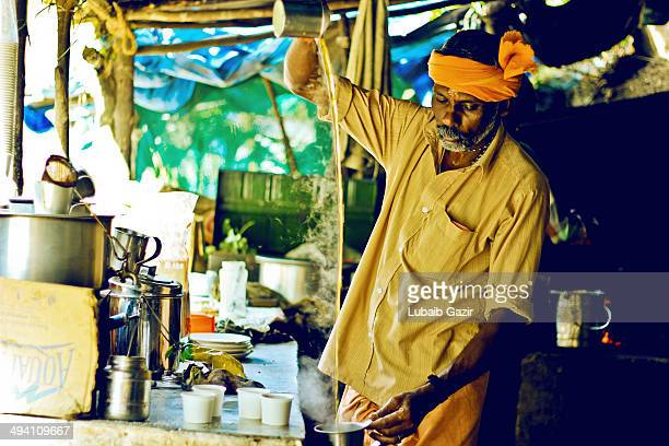 CONTENT] A waiter brews tea to be served inside a local tea shop in a village in Kerala