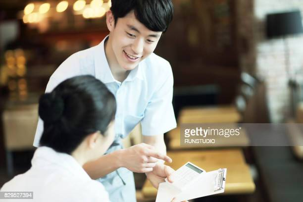 waiter bringing bill to table - klanten georiënteerd stockfoto's en -beelden