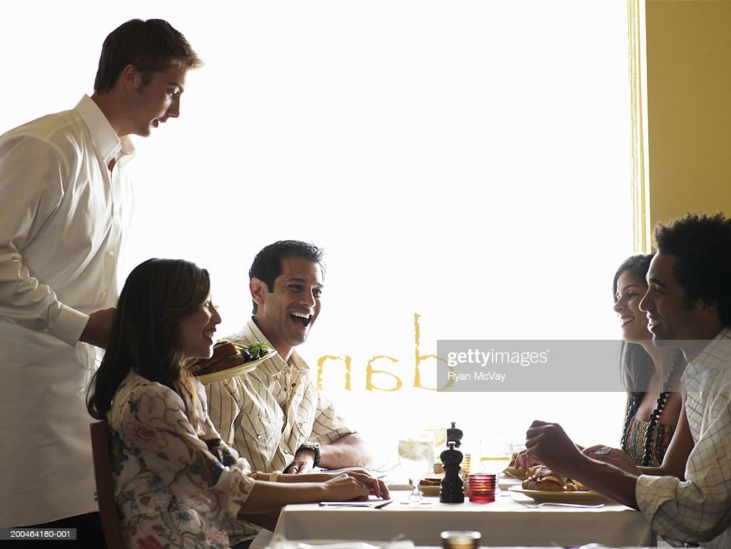 Waiter bringing plates of food to four adults in restaurant, side view : Stock Photo