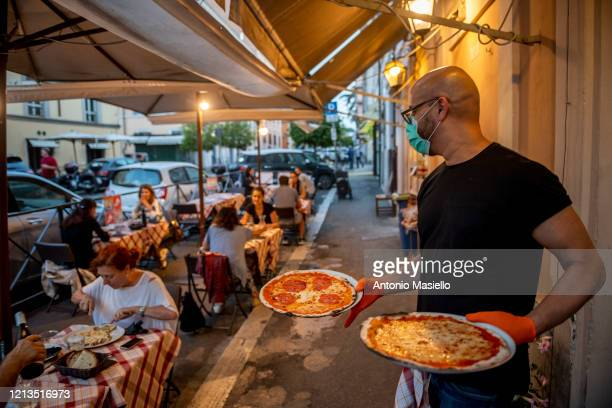 A waiter brings the pizzas to the people of the restaurant at Trattoria and Pizzeria Luzzi near Colosseo after two months of closure during Italy's...
