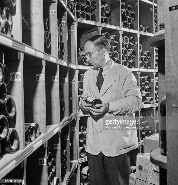 A waiter browsing bottles in the cellar of the 21 Club restaurant and speakeasy on West 52nd Street in New York City US September 1945