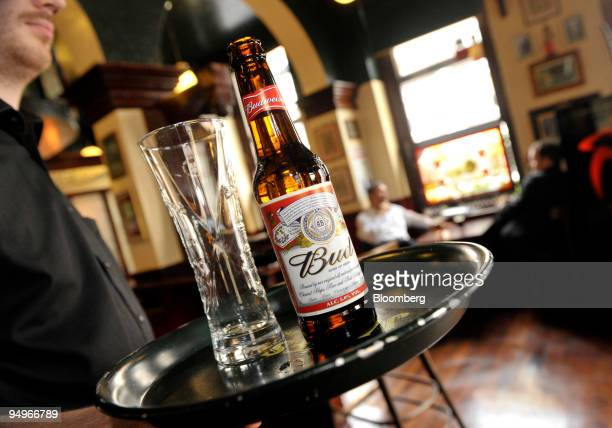Waiter carries a bottle of Budweiser beer and a glass at a bar in Brussels, Belgium, on Thursday, Aug. 13, 2009. Anheuser-Busch InBev NV, the world?s...