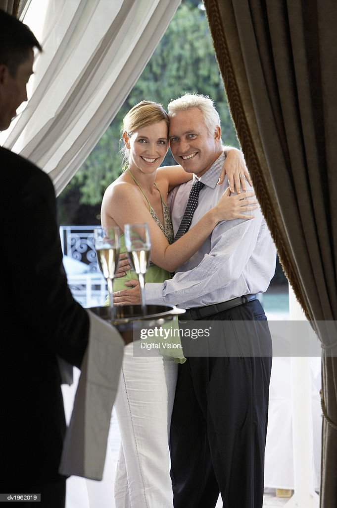 Waiter Carries a Tray of Champagne to a Well-Dressed Couple, Embracing : Stock Photo