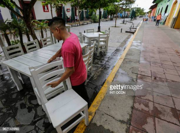 Waiter carries chairs outside an empty restaurant in Granada, 45 km from Managua, on May 22, 2018. - Almost all of the tourists have fled from...