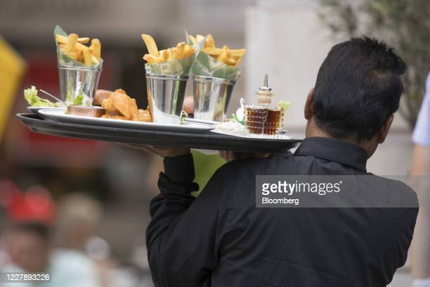 Waiter carries food to a table in an outdoor seating area of The Ivy Grill in London, U.K., on Monday, Aug. 3, 2020. On Monday, Chancellor of the...