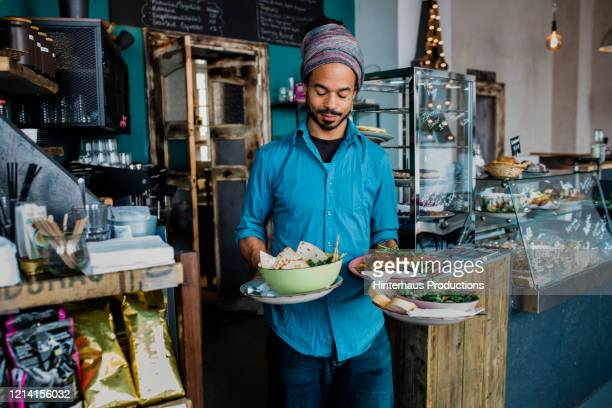 waiter carrying bowls of food to customers in cafe - vegetarianism stock pictures, royalty-free photos & images