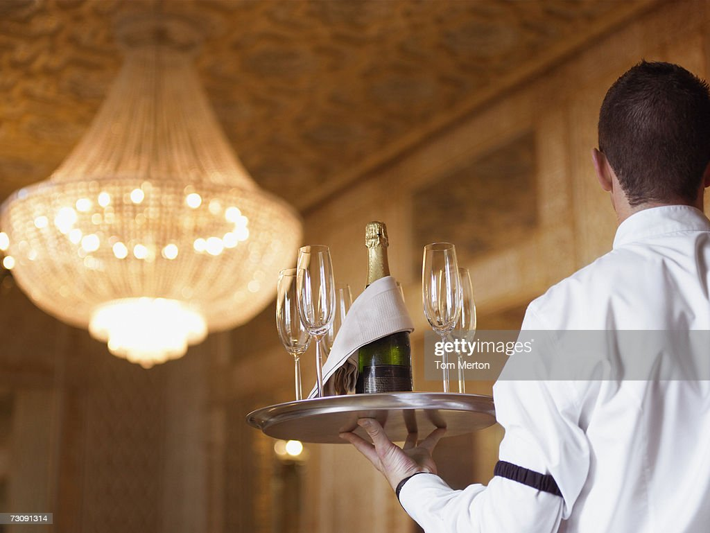 Waiter carrying Champagne on tray in hotel, rear view : ストックフォト