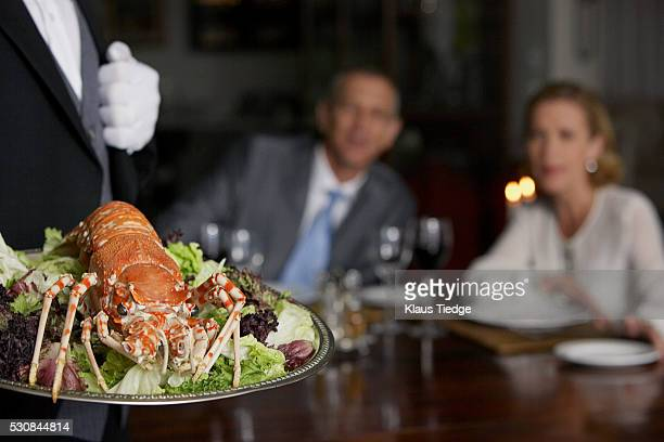 Waiter carrying lobster on serving plate