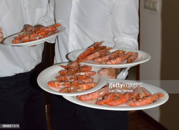 waiter carrying plates of prawns