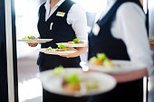 Waiter carrying plates with meat dish