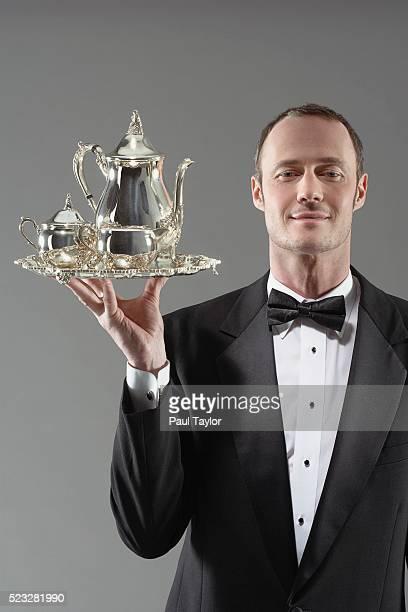 Waiter carrying silver tea set