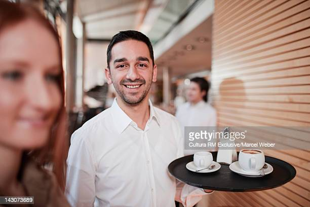 Waiter carrying tray in cafe