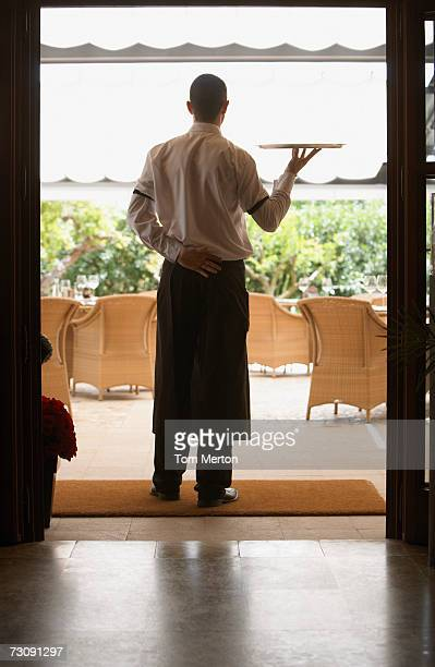Waiter carrying tray in restaurant, rear view