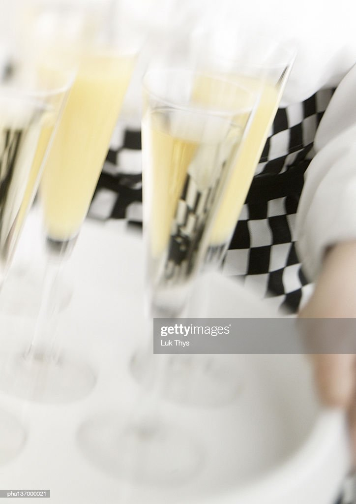 Waiter carrying tray of Champagne, blurred motion, close-up. : Stockfoto