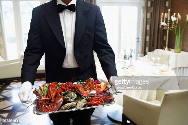 waiter carrying tray of seafood - aragosta foto e immagini stock
