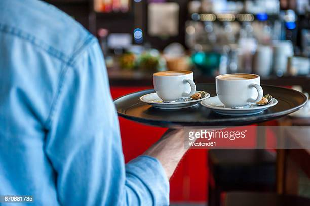 waiter carrying tray with cappuccino cups in a cafe - wait staff stock pictures, royalty-free photos & images