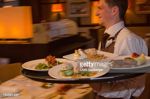 Waiter carrying tray with dishes through resturant