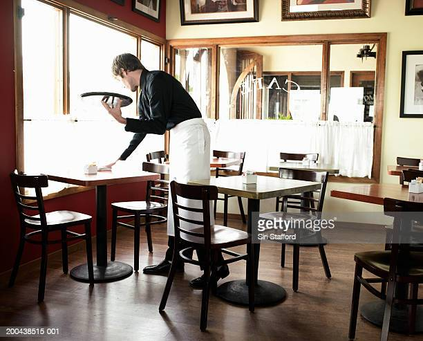 Waiter cleaning table in coffee shop