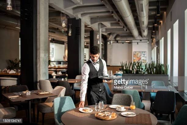 waiter cleaning tables in the restaurant - hotel stock pictures, royalty-free photos & images