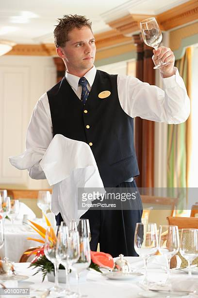 Waiter cleaning wine glasses