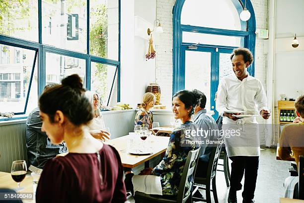 Waiter clearing plates at table in restaurant