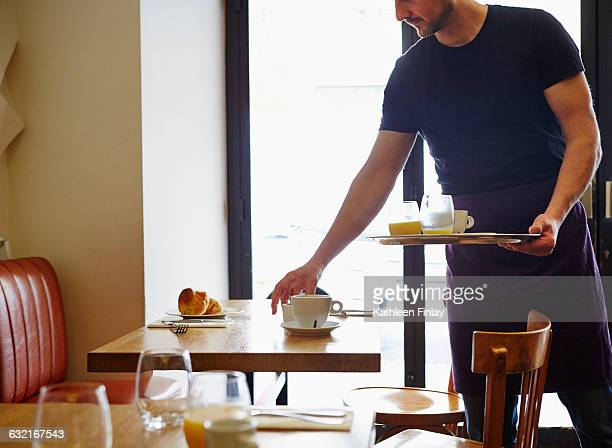 Waiter clearing table in restaurant