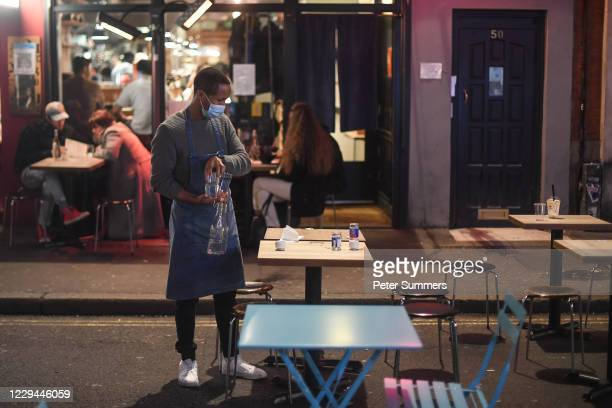 Waiter clears glasses from a table outside a restaurant on November 3, 2020 in London, England. Non-essential businesses, including pubs and...