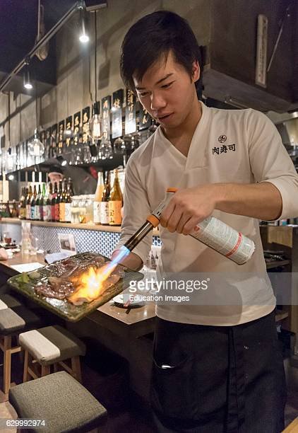 Waiter cooks fresh meat with a blowtorch in a restaurant in Kabukicho Tokyo Japan