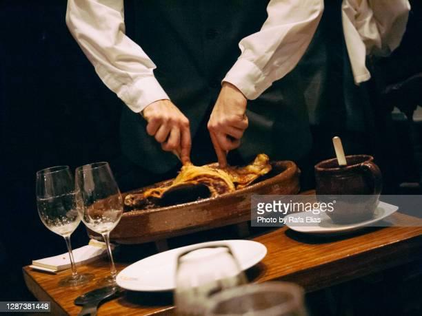 waiter cutting grilled piglet - comunidad autónoma de castilla y león fotografías e imágenes de stock