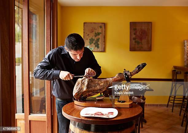 Waiter cutting serrano ham by hand