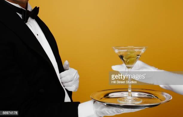 waiter delivering martini to customer - handschoen stockfoto's en -beelden