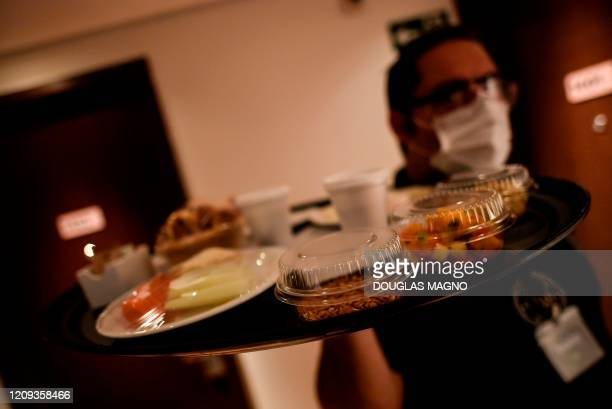 A waiter delivers a room service at a hotel in Belo Horizonte Brazil on April 7 2020 who continues to operate despite de novel coronavirus pandemic...