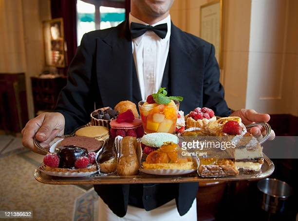 Waiter displaying French desserts on tray