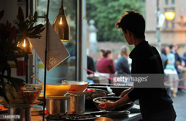 A waiter displays dishes during the aperitif hour in a bar in Rome on April 27 2012 Many Italian bars offer an 'Aperitivo' with an all you can eat...